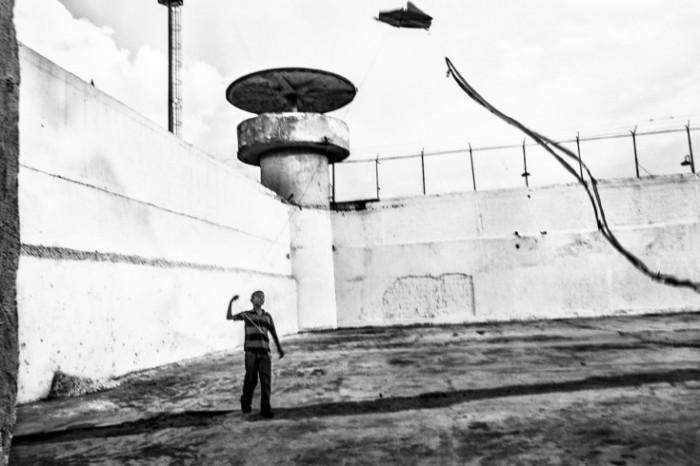 Un niño vuela un papagayo frente a un puesto de seguridad de la Guardia Nacional Bolivariana, la agencia oficial responsable por la seguridad de las prisiones en Venezuela. Foto: Sebastián Liste