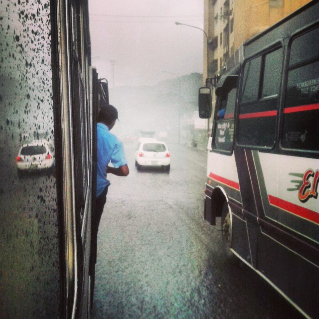 Camionetica en un día lluvioso con pasajero en la puerta. Foto @victor_53